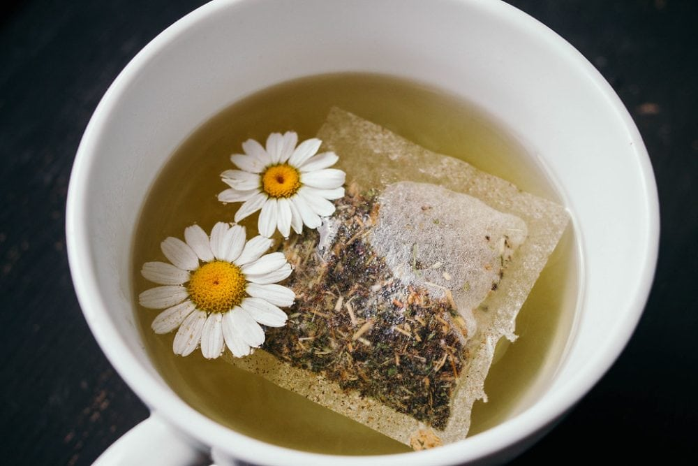 Chamomile tea bag and flowers