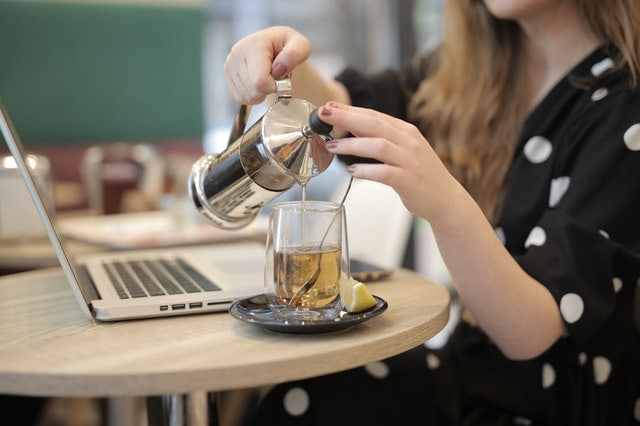 woman pouring hot decaf green tea into a glass
