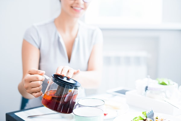 Pouring tea from a glass tea kettle