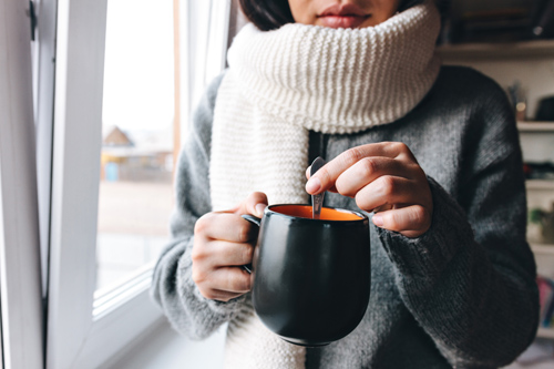 young woman stirs a hot tea