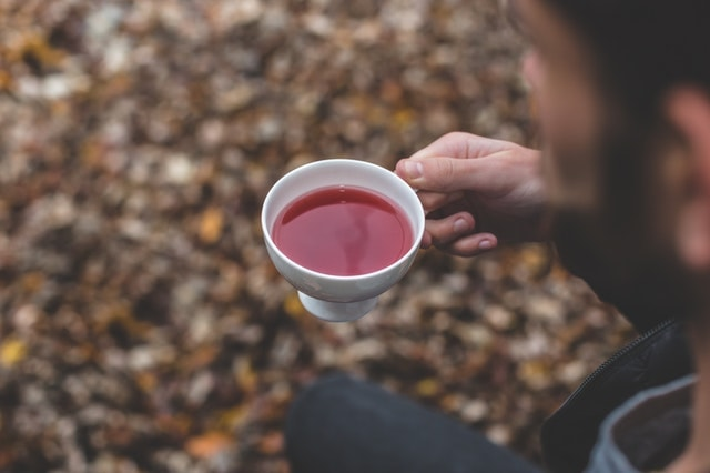Person holding cup of black tea