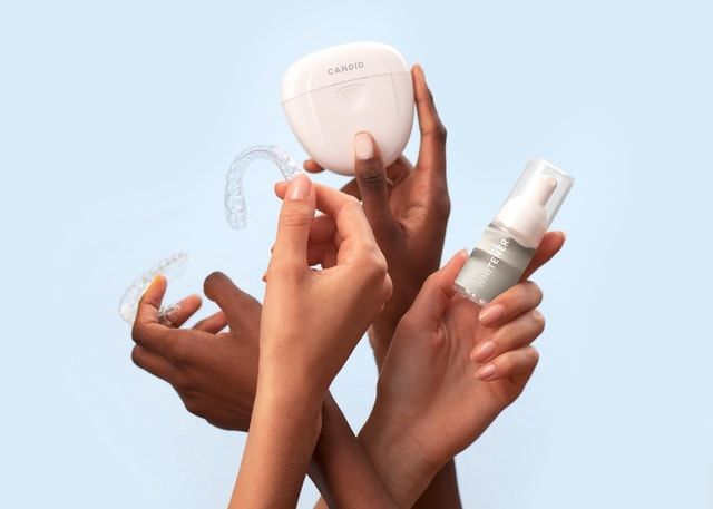 Hands holding retainers and cleaning kit