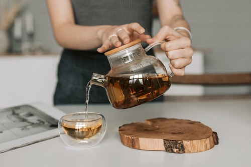 Lady Pouring Black Tea From Glass Tea Pot