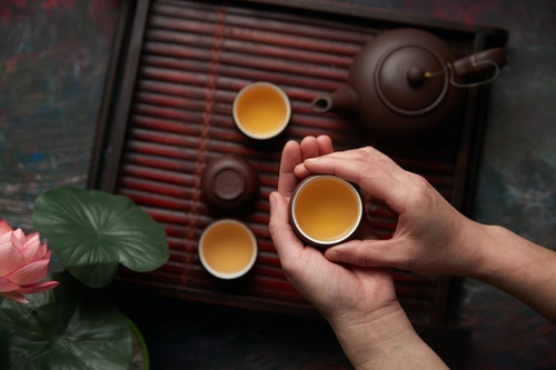 Person holding green tea served in brown ceramic cups