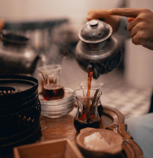 Person pouring tea from antique teapot