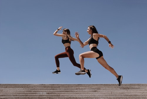 Two Women Jumping Over The Staircase