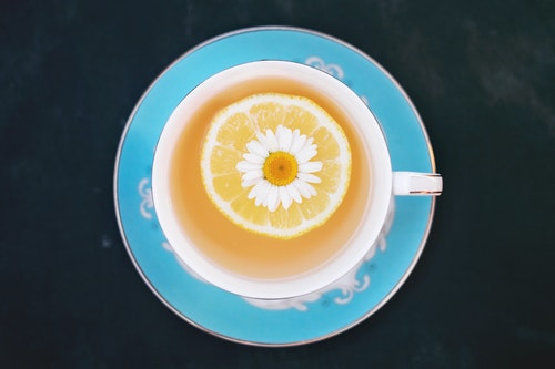 White Flower and Piece of Orange Dipped into Tea
