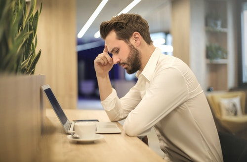 man with a headache caused by excess caffeine