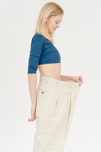 Cheerful slim woman in oversized pants
