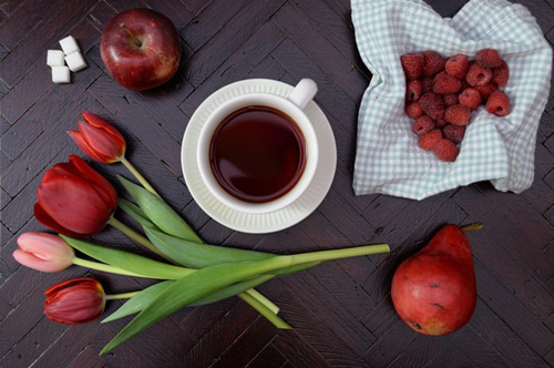 Fresh raspberry tea along with red fruits and flowers
