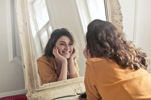 Woman smiling at the mirror